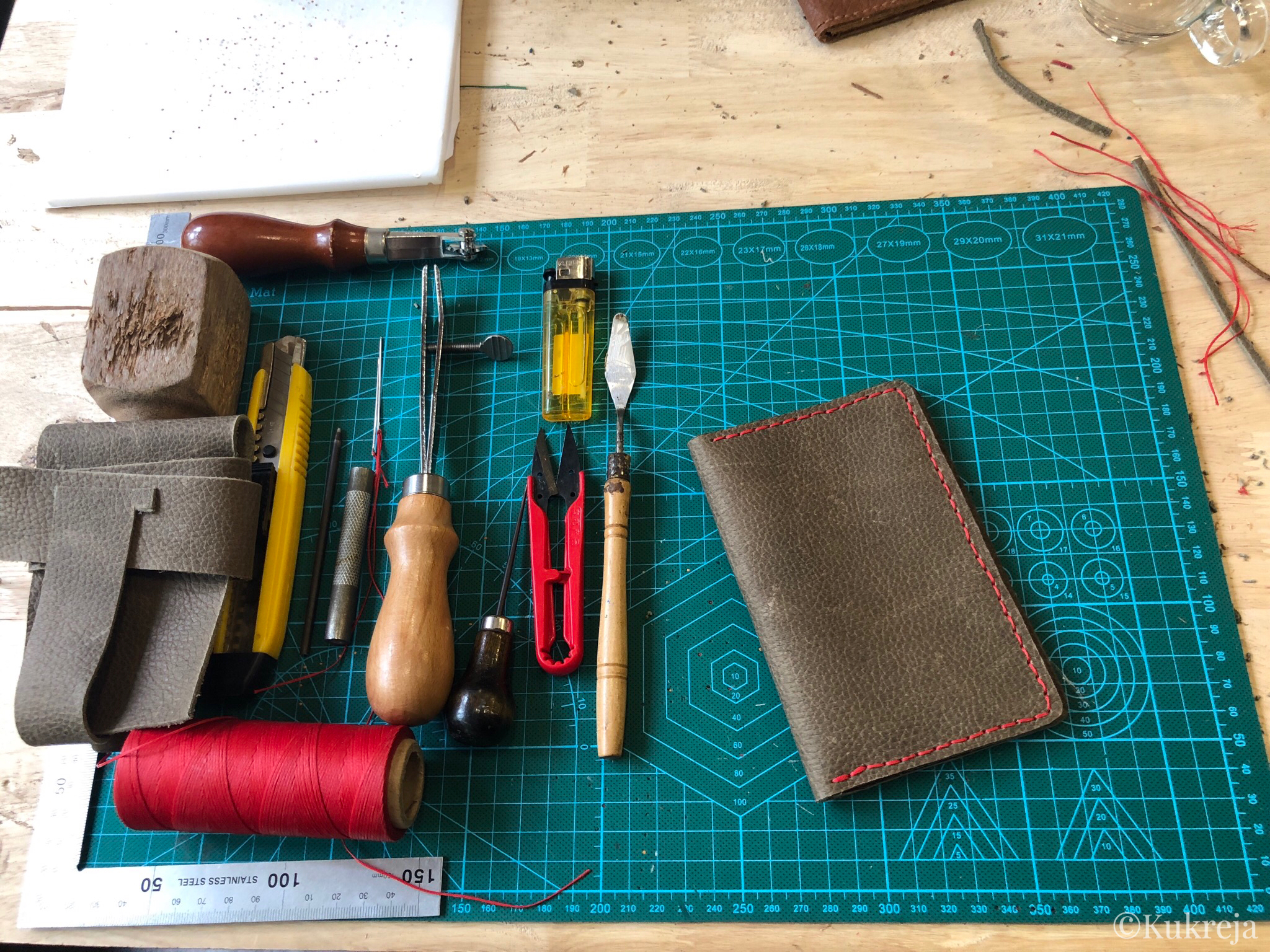Tools for leather craft displayed on the worktable along with the finished leather passport holder.